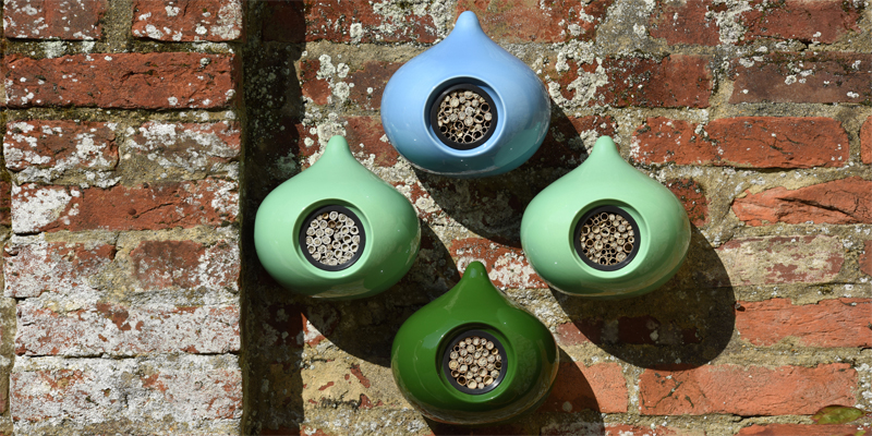 Beepalaces with nesting bees in blue, sage and ivy on a red brick wall